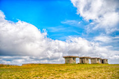 Small stony empty houses on green grass and cloudy sky Stock Photo