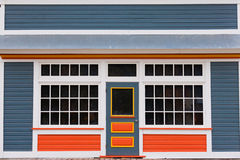 Small store front entrance colorful wooden house. Symmetrical view of the front door and entrance to a quaint colorful wooden house with large cottage pane Royalty Free Stock Images