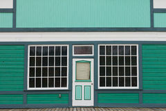 Small store front entrance to green wooden house. Symmetrical view of the front door and entrance to a quaint green wooden house with large cottage pane windows Stock Image