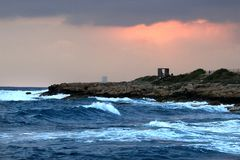 Wave storm splashing sea waterfront summer sunset clouds Royalty Free Stock Photos