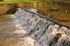 Small stream cascading over a weir Stock Images