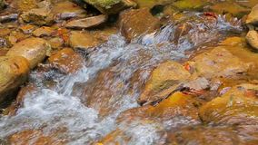 Small Stream Flowing Down Among Stones. Beautiful small mountain stream peacefully flowing among stones. This shot was made at waterfall Dzhur-Dzhur area in stock video footage