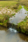 Small stream running on a green meadow with stones and smooth wa Royalty Free Stock Photo