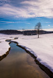 Small stream through a snow covered farm field in rural Carroll Stock Photo