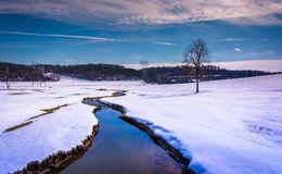 Small stream through a snow covered farm field in rural Carroll Stock Image