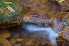 A small stream stained orange from acid mine drainage. Royalty Free Stock Photos