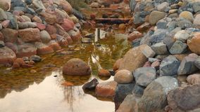 A small stream surrounded by stones stock video footage