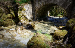 A small stream under a stone bridge Royalty Free Stock Photo
