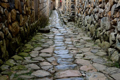 Small street extend, with stone wall and road Stock Images