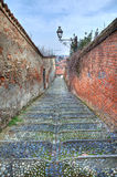 Small street among old walls in Saluzzo, Italy. Royalty Free Stock Photography