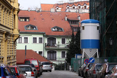 Small street in Prague. A house has being repaired. Small street in Prague. A house on the right side has being repaired Stock Photos