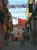 SMALL STREET IN VENICE. ITALY. CLOTHESLINES BETWEEN OLD HOUSES, WASHED CLOTHES HANGING ON CLOTHESLINES. MIDDLE THE COBBLED PAVEMENT TWO STONE WELLS Royalty Free Stock Images
