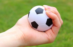 Small stress ball in hand on grass background Stock Photo