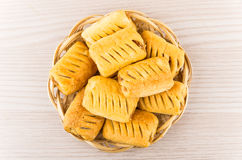 Small strudels in wicker basket on table Stock Image