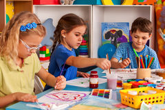 Small students children painting in art school class. Small students painting in art school class. Child drawing by paints on table. Boy and girls in royalty free stock image