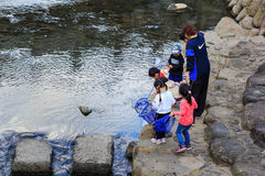 Small students collect garbage from the rive Stock Image