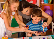 Small students finger painting in art school class. Small students with teacher finger painting in art school class. Teacher cheers children in kindergarten stock photo