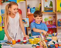 Small students girl and boy painting in art school class. Child drawing by paints on table. Male kid shows his drawing in kindergarten. Newcomer learns at new Royalty Free Stock Photo