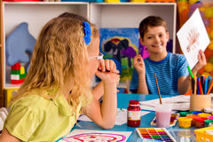 Small students girl and boy painting in art school class. Child drawing by paints on table. Male kid shows his drawing in kindergarten. Craft drawing education Stock Photography