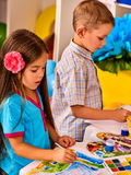 Small students girl and boy painting in art school class. Child drawing by paints on table. Portrait of kids in kindergarten. Craft drawing education develops Royalty Free Stock Photography