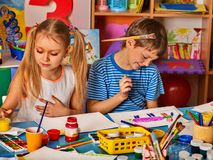 Small student child painting in art school class. Small students girl and boy painting in art school class. Child drawing by watercolor paints on table in royalty free stock images