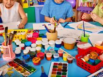Small students girl and boy painting in art school class. Children drawing by paints on table. Male kid shows his drawing in kindergarten. Preparing for a Royalty Free Stock Photo