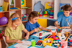 Small students girl painting in art school class. Small students girls painting in art school class. Children boy and girl drawing by paints on table. Children royalty free stock image