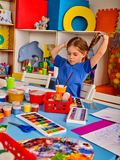 Small students girl painting in art school class. Small student girl painting in art school class. Child drawing by paints on table. Girl in an orphanage. Craft royalty free stock images