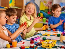 Small students girl finger painting in art school class. Small students with teacher finger painting in art school class. Break school in painting class. Mom royalty free stock photo