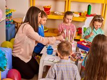 Small students with teacher painting in art school class. Royalty Free Stock Photography