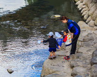 Small students to collect garbage from the rive Royalty Free Stock Photos