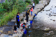 Small students to collect garbage from the rive Stock Image