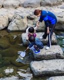 Small students to collect garbage from the rive Royalty Free Stock Images