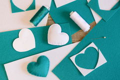 Small stuffed hearts toys. Hearts made of felt, thread, felt sheets, needle on wooden table. Simple handmade crafts Royalty Free Stock Photo
