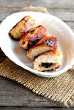 Small stuffed turkey meat rolls on a plate and on old wooden table. Fried turkey breast rolls with cheese and agaricus. Stock Images