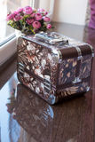 Small suitcase for jewelry.Beautiful flowers for the holiday Royalty Free Stock Photos