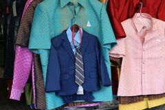 Small suits for children hanging with adult clothes for sell stock images