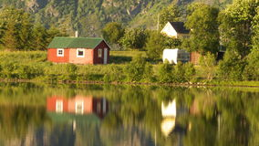 Small summer cabin mirroring. In a fjord of lofoten islands enlighted by the midnight's sun stock image