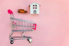 Yoy house and car in shopping cart on pink background. Small supermarket grocery push cart for shopping toy miniature white house and car on pink pastel color royalty free stock image
