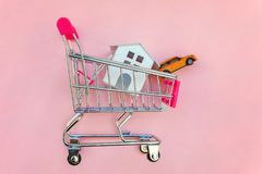 Yoy house and car in shopping cart on pink background. Small supermarket grocery push cart for shopping toy miniature white house and car on pink pastel color stock photos
