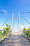 Small suspension bridge on blue sky, Mekong Delta, Vietnam. Stock Photos