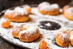 Small sweet croissants and candy sprinkled with powder sugar Stock Photos