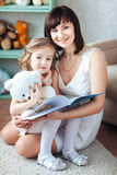 A small sweet little blonde daughter sits at her mother`s lap, reads a book and smiles Stock Photography