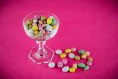 Small sweets. Colorful tiny raisin sweets in glass cup on pink background Royalty Free Stock Image