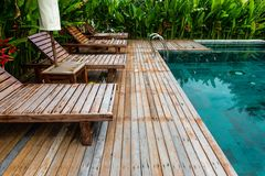 Small swimming pool with wooden setting surrounded by trees Stock Image