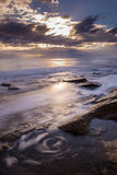 Small swirl on the beach with dramatic sky.Corfu Greece.  Stock Images