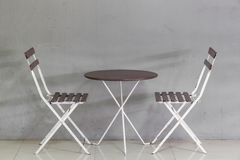 Small table and chairs near grunge wall Stock Photo