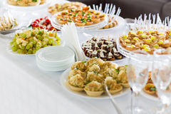 A small table with  a delicious buffet of canapes, caviar, sandwiches Royalty Free Stock Image
