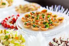 A small table with  a delicious buffet of canapes, caviar, sandwiches Royalty Free Stock Photo