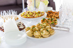 A small table with  a delicious buffet of canapes, caviar, sandwiches Royalty Free Stock Photos